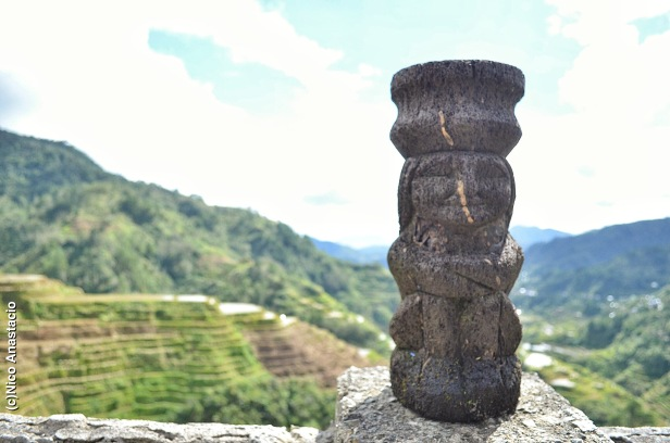 a stone statue and the Banaue Rice terraces as its backdrop