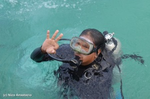 Scuba diver teaching the tourists the proper  hand signs during helmet diving