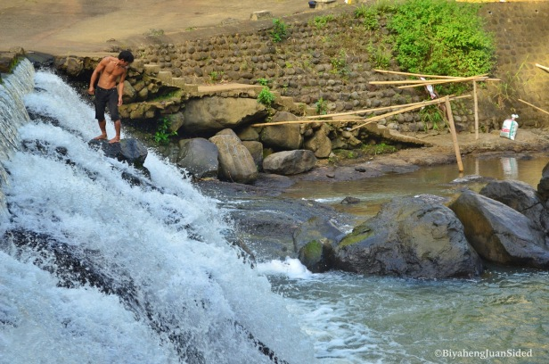 a person taking a bath at the falls at the ecopark